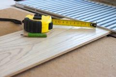 Pomiarowa taśma i ołówek na laminat podłogowej desce Fotografia Stock