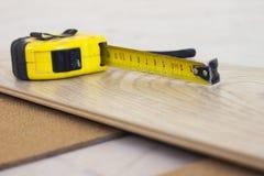 Pomiarowa taśma na laminat podłogowej desce Fotografia Stock