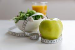 Pomiarowa taśma wokoło jabłka, pucharu zielona sałatka i szkła sok, Ciężar strata i prawy odżywiania pojęcie Zdjęcie Stock