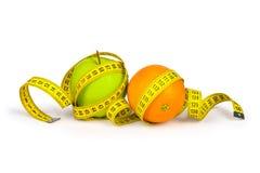 Pomiarowa taśma wokoło zieleni jabłka i pomarańcze Zdjęcie Stock