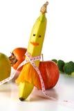 Pomiarowa taśma zawijająca wokoło banana w postaci dziewczyny, z jabłkiem, brokułami i marchewką, Pojęcie dieta Zdjęcie Royalty Free