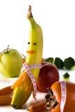 Pomiarowa taśma zawijająca wokoło banana w postaci dziewczyny, z jabłkiem, brokułami, marchewką i kaki, Pojęcie dieta Zdjęcia Stock