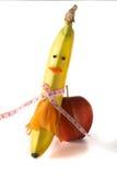 Pomiarowa taśma zawijająca wokoło banana w postaci dziewczyny, z jabłkiem odizolowywającym na białym tle, pojęcie dieta Zdjęcia Stock