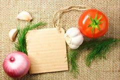 Pomidor, cebula i czosnek z kartonową metką na grabić bac, Zdjęcia Royalty Free