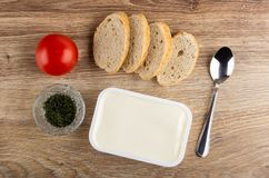 Pomidor, kawałki chleb, puchar z wysuszonym koperem, biały plastikowy słój z rozciekłym śmietankowym serem, łyżka na drewnianym s zdjęcie royalty free