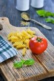 Pomidor, makaron i ziele na drewnianej desce, Zdjęcia Stock