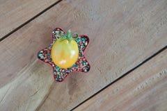 Pomidor na kolorowym użyźniaczu w czerwieni gwiazdy kształcie na drewnianym stołowym tle Zdjęcia Stock