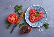 Pomidor, sól, pietruszka i nóż na szarość, betonujemy tło zdjęcie stock