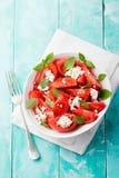 Pomidorowa sałatka z basilu, sera, oliwa z oliwek i czosnku opatrunkiem, tła drewniany błękitny Odgórny widok Obrazy Royalty Free