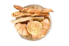 Pomidorowi chlebowi kije, croissants i babeczka w drewnianym talerzu na białym tle, zdjęcia royalty free