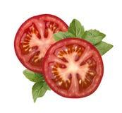 Pomidorowy plasterek i basil odizolowywający na białym tle fotografia royalty free