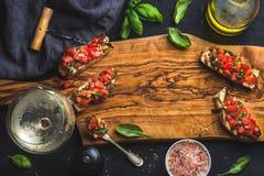 Pomidoru i basilu bruschetta z szkłem biały wino, oliwa z oliwek, sól, świezi ziele na drewnianej desce nad czarnym tłem zdjęcie royalty free