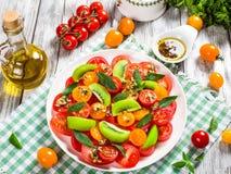 Pomidoru, kiwifruit i mennicy sałatka z butelką oliwa z oliwek, Obrazy Stock