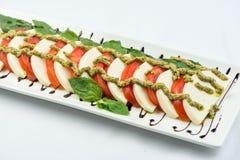 Pomidory coarsely siekali z serem, na obciosują talerza na białym tle zimne przekąski obraz stock