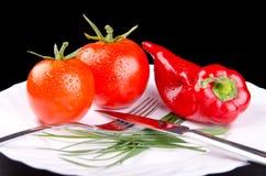 Pomidory i pieprz w talerzu Fotografia Stock