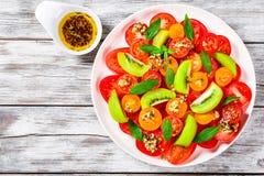 Pomidory, kiwi owoc, nowa sałatka ubierali z tartym serowym br Zdjęcia Stock