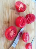 Pomidory na bambus desce z nożami Obraz Stock