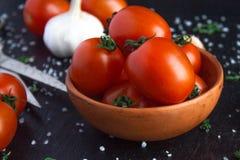 Pomidory w naczyniu na czarnym tle obraz stock