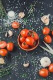 Pomidory w naczyniu na czarnym tle zdjęcia stock
