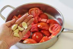 Pomidory w rondlu z czosnkiem Obrazy Stock