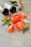 Pomidory z czosnkiem i pikantność na stole Zdjęcia Stock