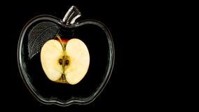 Pomme coupée en tranches dans un bol en verre sur un fond noir Photo stock