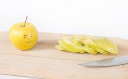 Pomme coupée en tranches et une pomme effrayée à côté de elle avec un regard doux Photographie stock libre de droits