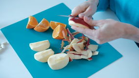 Pomme de nettoyage de femme avec le couteau dans la cuisine préparant le petit déjeuner sain banque de vidéos