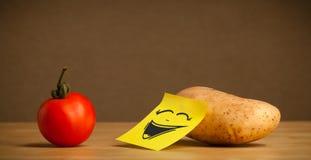 Pomme de terre avec la note de post-it riant sur la tomate Photos libres de droits