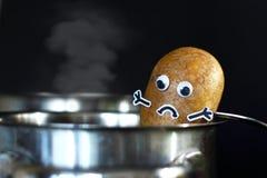 Pomme de terre avec les yeux tristes de visage et de lunettes étant mis dans un pot de cuisson à la vapeur sur le fond noir foncé images stock