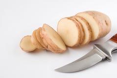 Pomme de terre coupée en tranches et couteau d'isolement Photos stock