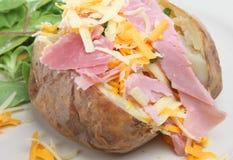 Pomme de terre cuite au four avec du jambon et le fromage Photographie stock