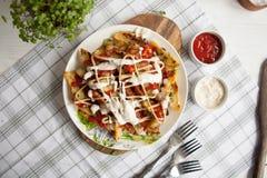 Pomme de terre cuite au four avec les verts, l'ail et les sauces d'un plat blanc photographie stock libre de droits