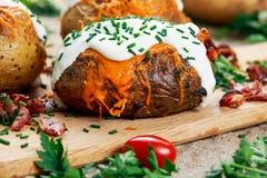 Pomme de terre cuite au four chaude avec du fromage, le lard, la ciboulette et la crème sure Photos stock
