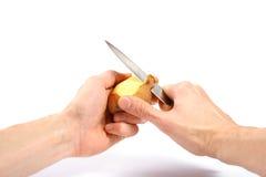 pomme de terre de peau de mains avec le couteau Photographie stock libre de droits