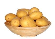 Pomme de terre de primeurs dans la cuvette en bois d'isolement sur le fond blanc Image libre de droits