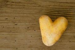 Pomme de terre en forme de coeur sur le vieux conseil en bois impeccable Images stock