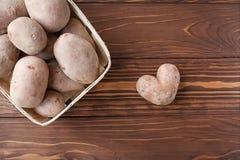 Pomme de terre et panier en forme de coeur avec des pommes de terre Photos stock