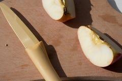 Pomme et couteau de tranches au soleil images libres de droits
