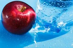 Pomme et eau en bouteille rouges Photographie stock libre de droits
