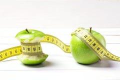 Pomme et tronçon verts de pomme avec la bande jaune de centimètre sur le blanc Photos stock