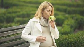 Pomme femelle enceinte de consommation avec dégoût, nausée de sentiment, nutrition saine banque de vidéos