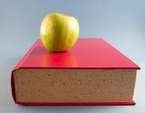 Pomme jaune avec le livre rouge Photos libres de droits