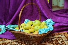 Pomme jaune et verte dans le panier Panier des pommes vertes sur lesquelles sont les points et les traces noirs évidents des vers photographie stock