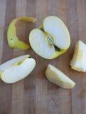 Pomme jaune se trouvant sur un conseil en bois Photographie stock libre de droits