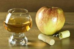 Pomme juteuse avec l'ouvreur de vin et le verre de jus de pomme frais sur une table en bois Images stock