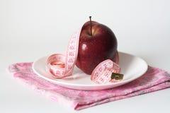 Pomme juteuse rouge et bande de mesure de plaque Images stock