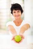 Pomme mûre de femme Image stock