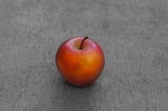 Pomme mûre rouge sur le fond blanc noir Image libre de droits