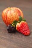 pomme, mûre et fraise sur une surface en bois Image libre de droits